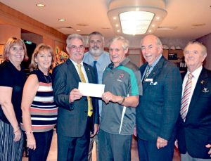 Photo of Ernie Speed receiving his $300 cheque